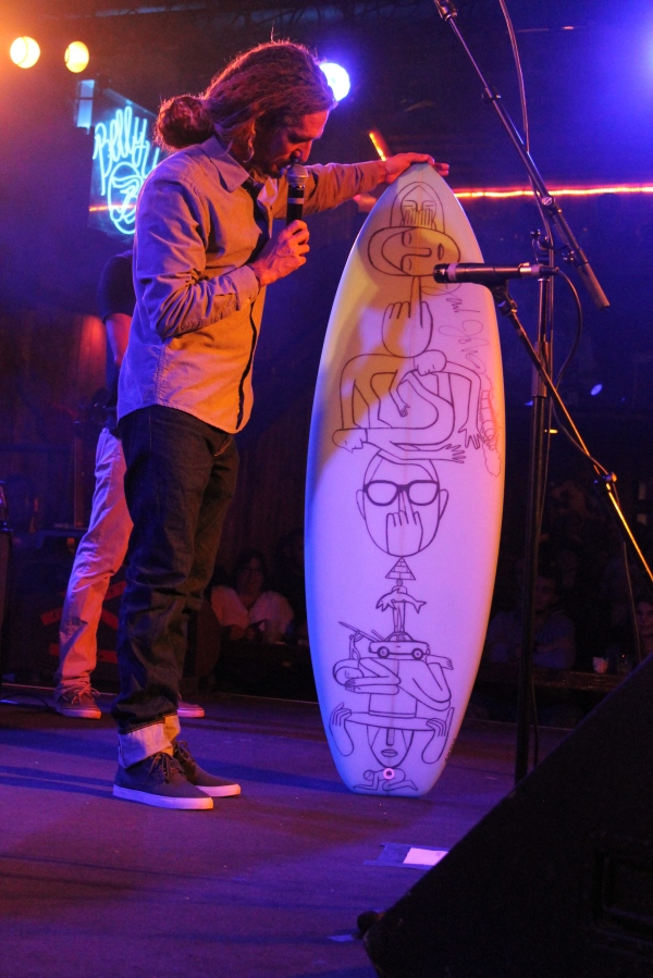 Rob Machado holding up a custom surfboard auctioned off for $4000